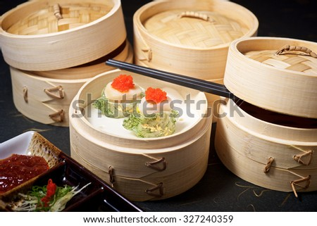 Gourmet Yumcha Dimsum Set in bamboo container with chopstick on black ground - stock photo