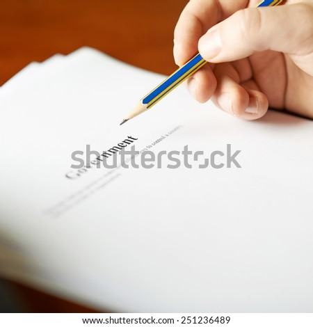 Government definition as a shallow depth of field close-up composition of a man in a business suit working with the text - stock photo
