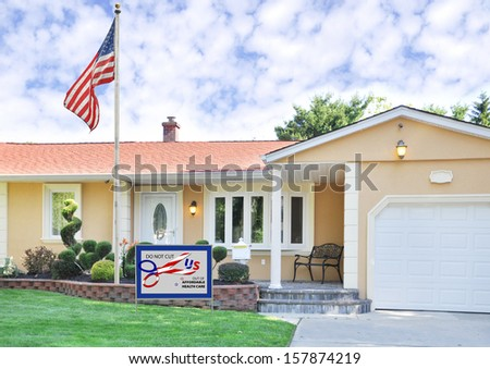 "Government Shutdown Political Message ""DO NOT CUT US OUT OF AFFORDABLE HEALTH CARE"" on Front Yard Lawn Suburban Home with American Flag - stock photo"