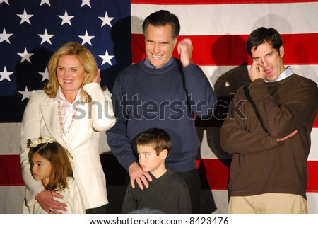 Governor Mitt Romney campaigning with family, all fingering something - stock photo