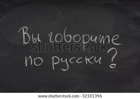 Govorite po russki? Do you speak Russian question handwritten in cyrillic alphabet with white chalk on a blackboard with eraser smudges