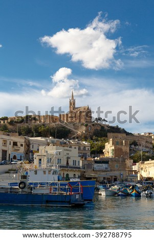 GOZO, MALTA - OCTOBER 31, 2015 : General seascape view of Gozo island in Malta with boats around, on cloudy blue sky background.
