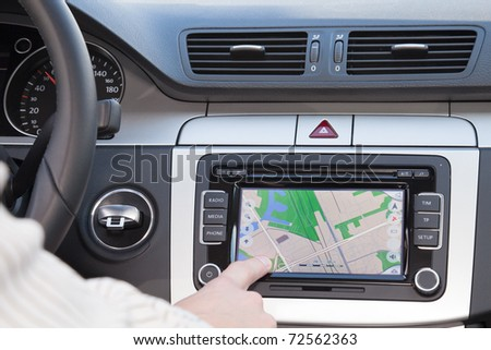 GPS navigation panel on dashboard inside a car. Finger pointing on destination point.