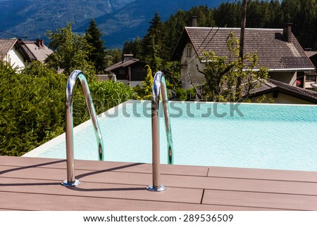 Grab bars ladder in blue swimming pool in a garden in Austria - stock photo