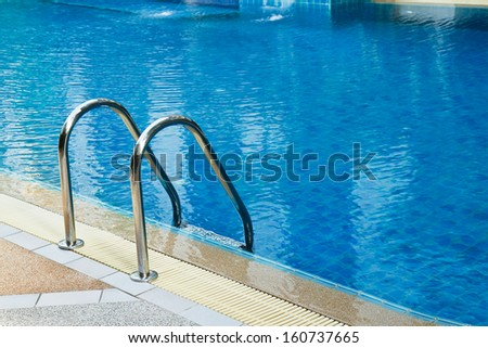 Grab bars ladder in  swimming pool - stock photo