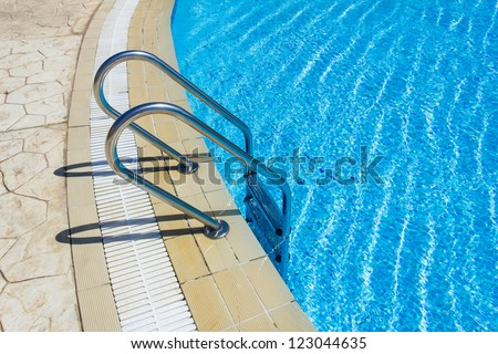 Grab bars ladder in the blue swimming pool - stock photo