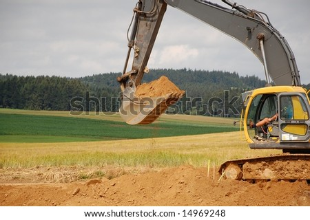 Grab it! Excavator with full dipper is waiting for a tuck to drop the soil in it.