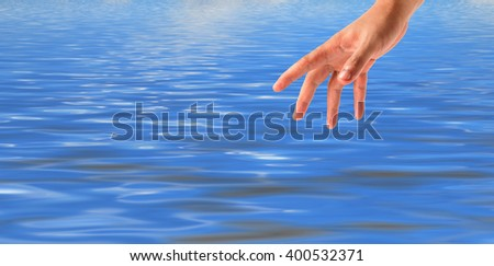 Grab the hand on sky-clouds and sea background. - stock photo