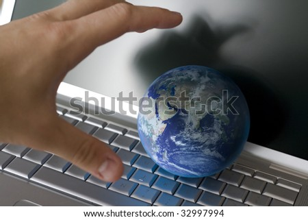 grabbing the world with my hand in front of a laptop