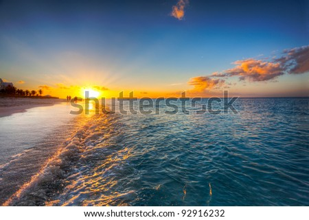 Grace Bay Beach, Turks & Caicos, with the setting sun at the horizon - stock photo