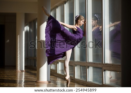 Graceful ballerina dancing in a purple dress leg lifted high, standing on pointe near a large window in the setting sun.