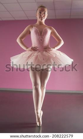 Graceful ballerina standing en pointe in the ballet studio - stock photo