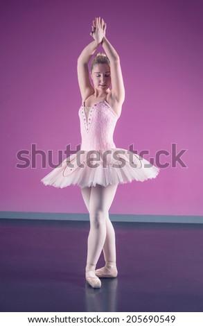 Graceful ballerina standing in fifth position in the ballet studio - stock photo