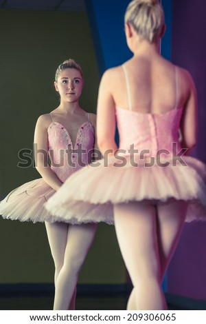 Graceful ballerina standing in first position in front of mirror in the ballet studio - stock photo