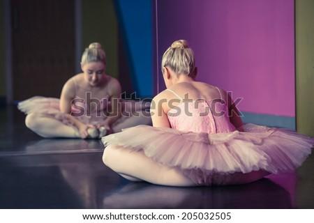 Graceful ballerina warming up in front of mirror in the ballet studio - stock photo