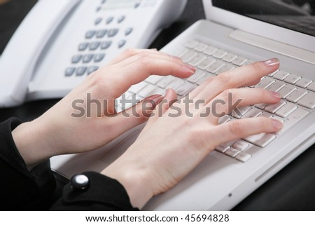Graceful female hands print the text on the keyboard of a computer - stock photo