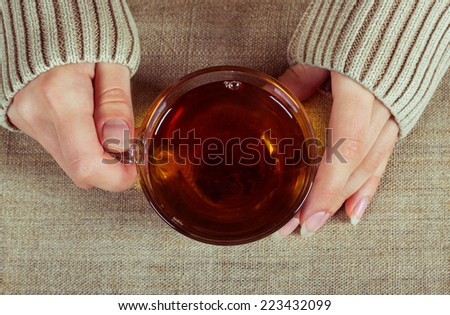 Graceful hands of a girl with a cup of tea and a long-sleeved shirt, symbolizing the comfort of home - stock photo