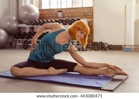 Graceful smiling woman working out in a gym on a mat doing stretching exercises , side view - stock photo