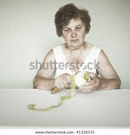 Gracious senior lady portrait cleaning an apple - stock photo