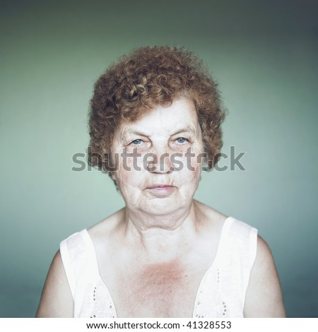Gracious senior lady portrait on green background - stock photo