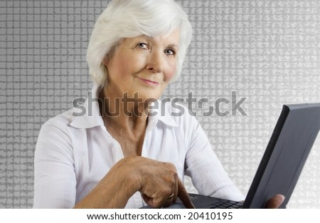 Gracious senior lady with laptop on grey background - stock photo