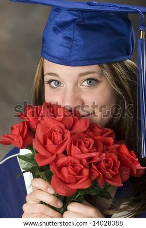 Grad portrait of cute girl, smelling her graduation roses. Studio shot. - stock photo