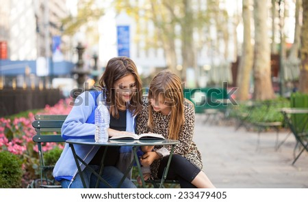 Grade  School girls sitting in a city park in new york reading a book with a bottle of water - stock photo