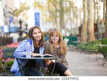 Grade  School girls sitting in a city park in new york reading a book with a bottle of water