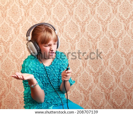 Gradeschool girl at home listening to music on a pair of vintage 1970s wired headphones reacts to the old style jack - stock photo