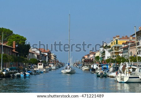GRADO, ITALY - OCTOBER 10, 2012 - Sailboat navigating in the fisher harbor of Grado, Italy