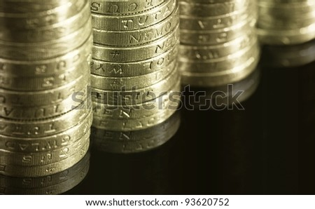 Gradually decreasing stacks of one pound english coins isolated on black background with reflection underneath
