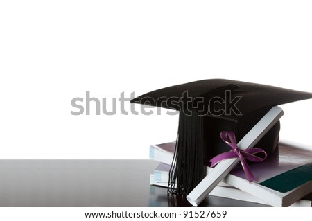 graduate certificate and graduate cap on a stack of books isolated on white - stock photo