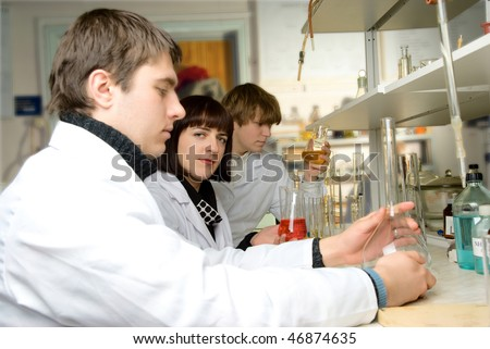 graduate - chemists in the lab with a teacher conducting experience with chemical reagents - stock photo