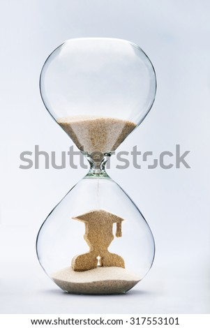 Graduate figure made out of falling sand inside hourglass - stock photo