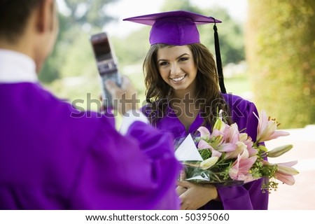 Graduate Having Picture Taken with Cell Phone outside - stock photo