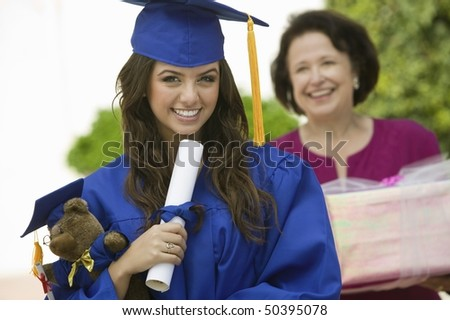 Graduate holding teddy bear and diploma outside, portrait