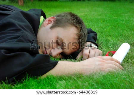 Graduate lay on the grass and closed his eyes - stock photo