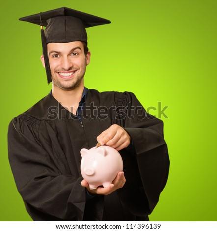 Graduate Man Holding Piggybank Isolated On Green Background - stock photo