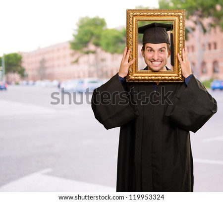 Graduate man looking through a frame, outdoor