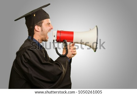 Graduate Man Shouting Into The Megaphone On Grey Background