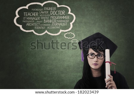 Graduate student in graduation cap is holding certificate thinks about her dream  - stock photo