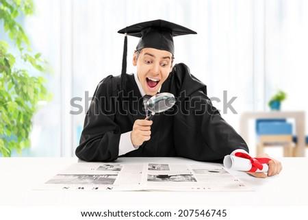Graduate student seeking job in newspaper at home  - stock photo