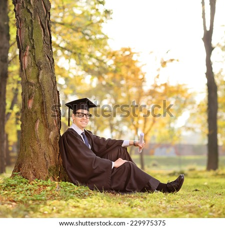 Graduate student sitting by a tree in a park shot with tilt and shift lens - stock photo