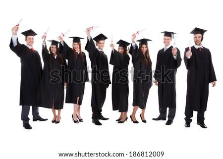Graduate students raising hands. Isolated on white background - stock photo