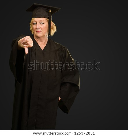 Graduate Woman Showing Thumb Down Sign On Grey Background - stock photo