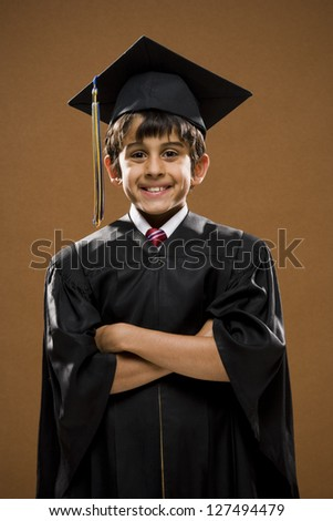 Graduated boy with mortarboard smiling with arms crossed - stock photo