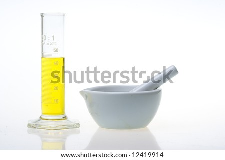graduated cylinder and grinding mortar isolated on white background - stock photo
