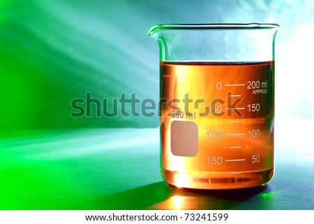 Graduated scientific glass beaker with amber orange chemical liquid over reflective background for a chemistry laboratory experiment in a science research lab