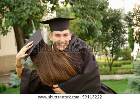 Graduates embrace and congratulate each other - stock photo