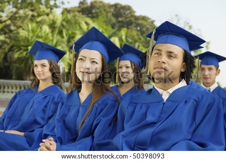Graduates listening to ceremony outside - stock photo